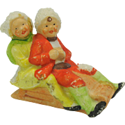 Vintage German bisque snowed cake decoration-boy and girl on sled