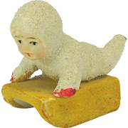 Vintage German snowed bisque Snow baby laying on sled