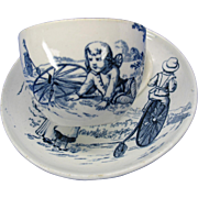 Antique cup and saucer-child on Penny Farthing Boneshaker bicycle