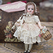 "7"" (18 cm) Antique German Mignonette doll in original dress for french market, with Paris Lafayette trunk"