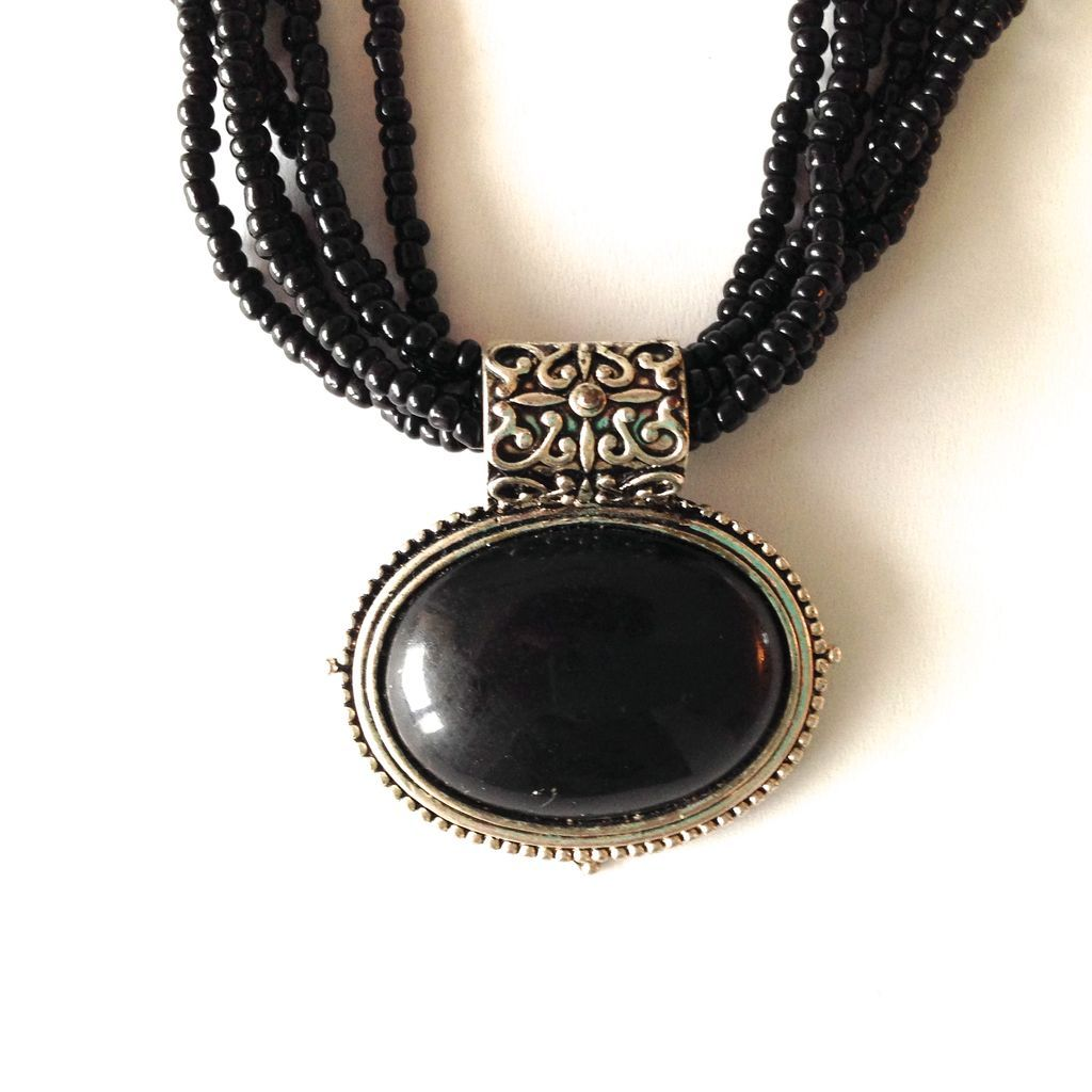 black and silver tone pendant on black beaded necklace