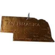 Brass Nebraska fob.  Die cut shape of the state. Whitehead and Hoag
