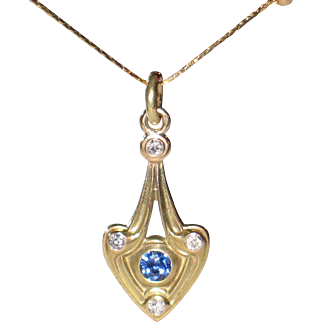 Natural blue sapphire and white diamonds pendant in 14k yellow gold.