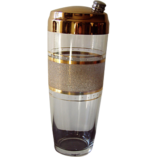 Clear glass cocktail shaker with brass lid