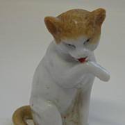 Antique miniature porcelain cat licking it's paw