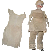"""Antique bisque doll house doll in original underclothes. Painted face, bisque arms & legs, cloth body. Very good condition. 5""""."""
