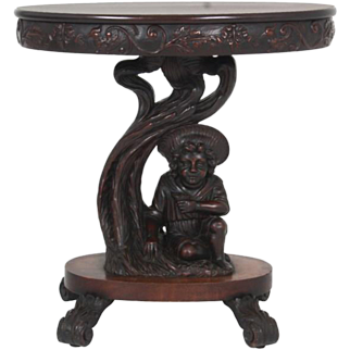 Figural carved oval mahogany center table with a carved skirt