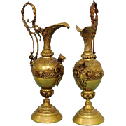 Pair of bronze ewers with griffins in ornate open work handles