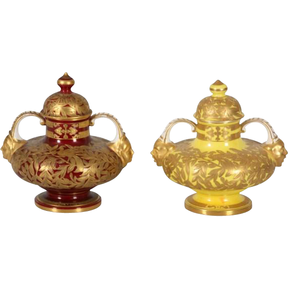 Pair of Royal Crown Derby covered urns with gold decoration and faces on handles