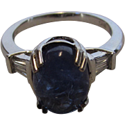 14 Karat White Gold Tanzanite Cabochon Ring Enhanced with Diamond Baguettes