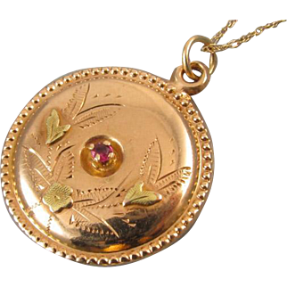 Antique Edwardian 14k ruby disc pendant necklace with hand engraved and green gold leaf and flower detail