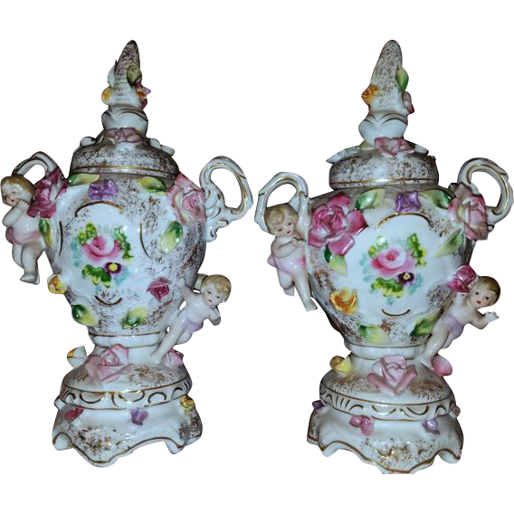 Outrageously ornate vintage antique porcelain ceramic cherub angel putti floral roses and dogwood eared covered pedestal footed urns