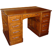 Quartered oak executive desk---raised panels, file drawer, carved pulls