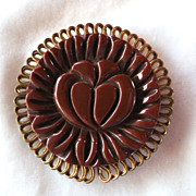 Carved brown bakelite and metal framed brooch