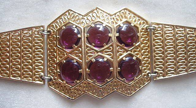 Wide gold tone filigree bracelet with faux amethyst glass cabochons