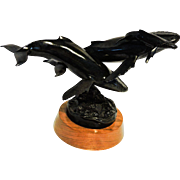 "Randy Puckett bronze sculpture of a black humpback whale family, titled ""Homecoming"""
