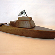 Handmade wooden pond boat with simple tin flag and pull-ring on bow.