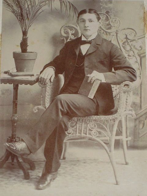 Antique Victorian Cabinet Card of Well Dressed Young Man Sitting in Wicker Chair holding a Book
