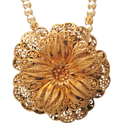 Vintage gold tone filigree pin on a faux pearl necklace