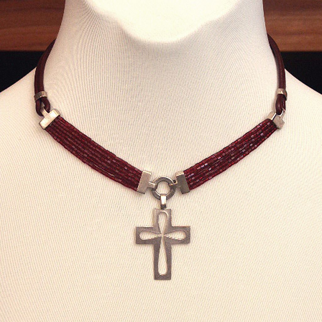 Cross silver pendant on contemporary leather necklace.